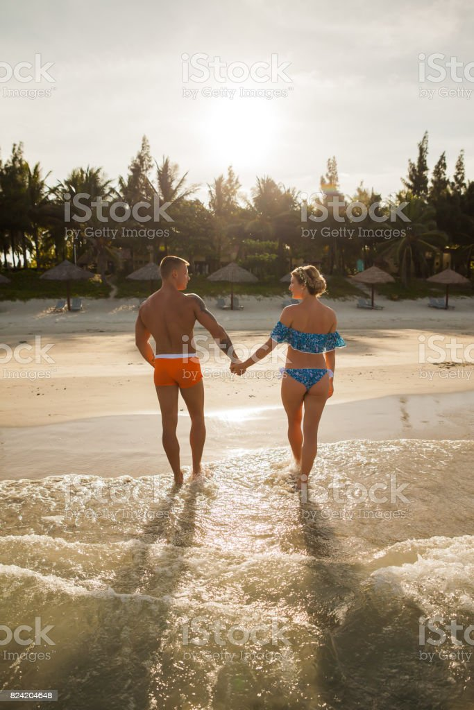 Couple walking out of sea water stock photo