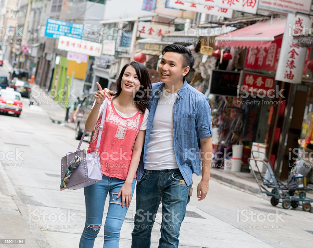 Couple walking through a flee market in Hong Kong royalty-free stock photo