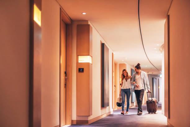 Couple walking through a luxury hotel corridor stock photo