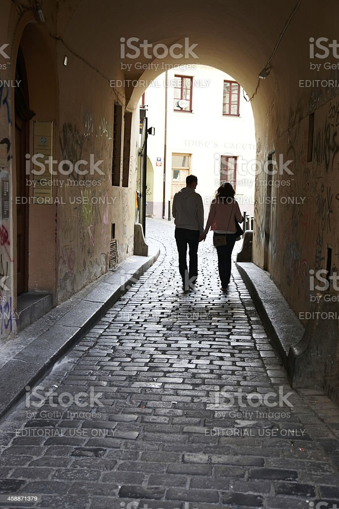 Couple walking through cobblestoned archway royalty-free stock photo