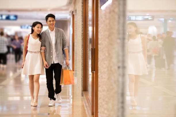 Couple walking through shopping mall Chinese woman and man in their 20s walking arm in arm through bright, modern retail centre, with bags, consumerism, retail shopping couple asian stock pictures, royalty-free photos & images