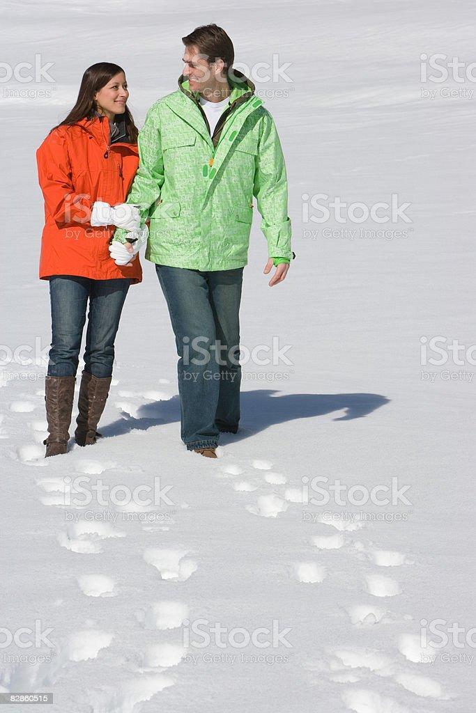 Coppia A piedi attraverso la neve foto stock royalty-free