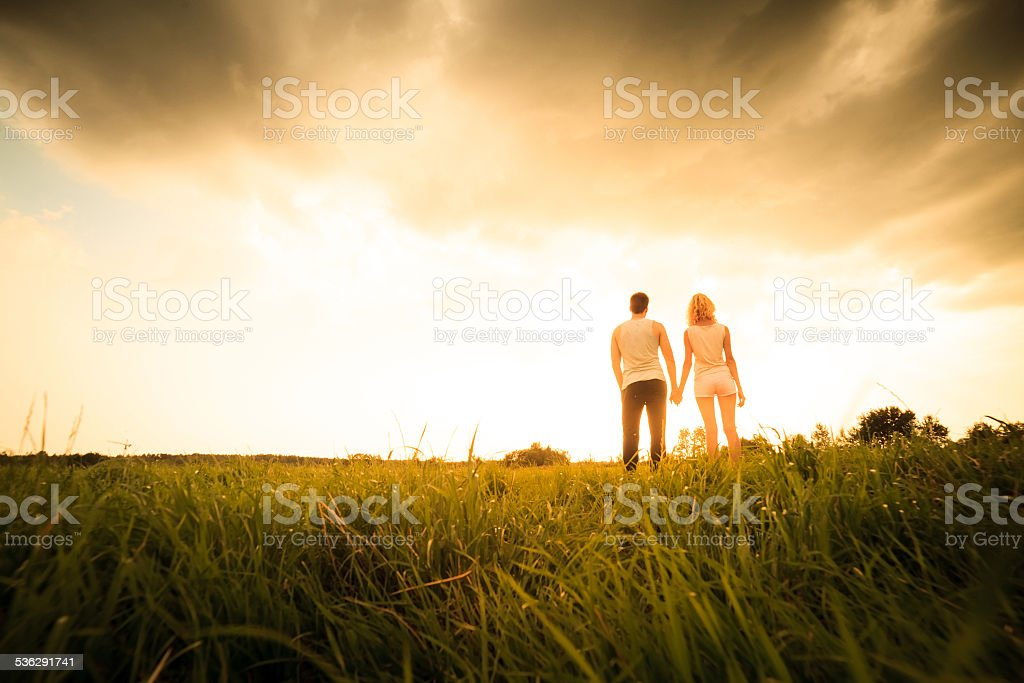 couple walking through the field and holding hands stock photo
