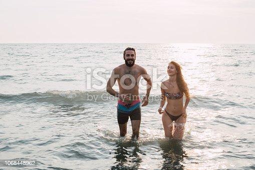Young couple walking through the sea