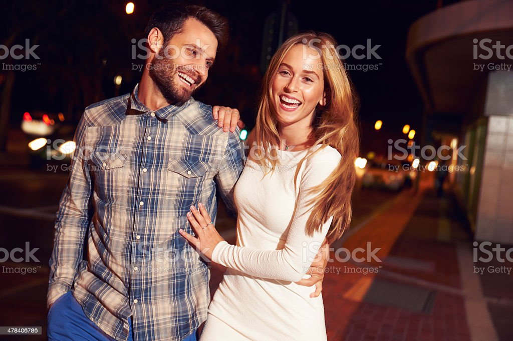 Couple walking through town together at night stock photo