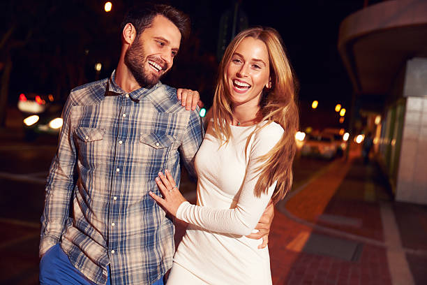 Couple walking through town together at night Couple walking through town together at night, smiling date night romance stock pictures, royalty-free photos & images