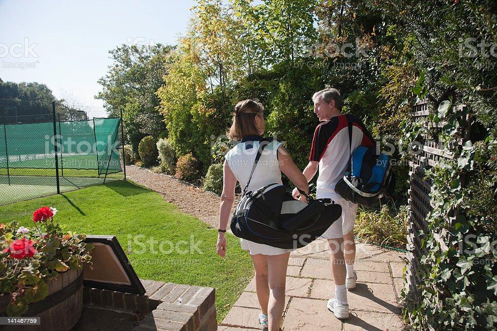 Couple walking to tennis courts stock photo
