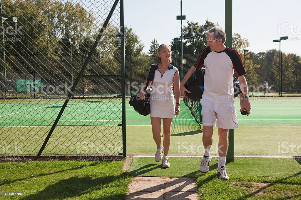 Couple walking to tennis courts stock photo