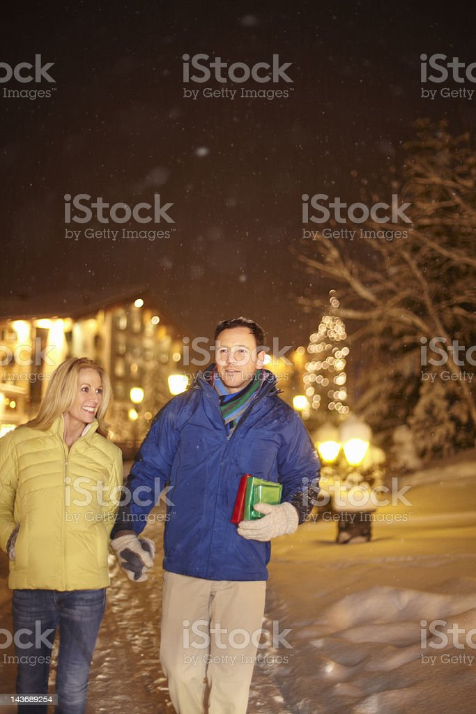 Couple walking together in snow royalty-free stock photo