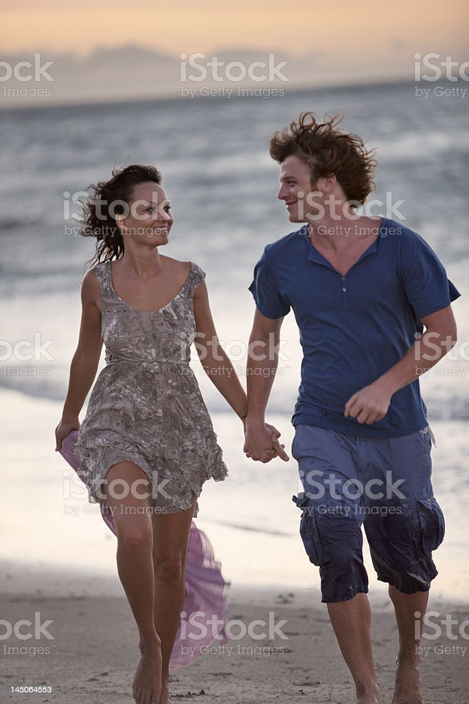 Couple walking together on beach stock photo