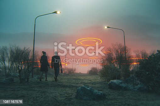 Couple walking towards flying UFOs.