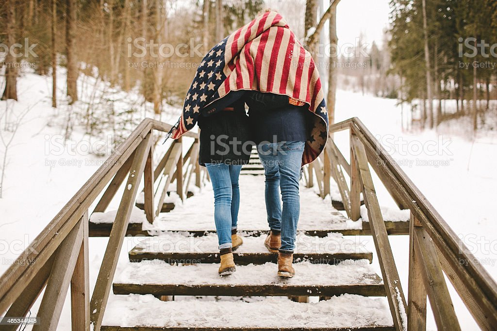Couple walking winter park under american flag style cloth stock photo