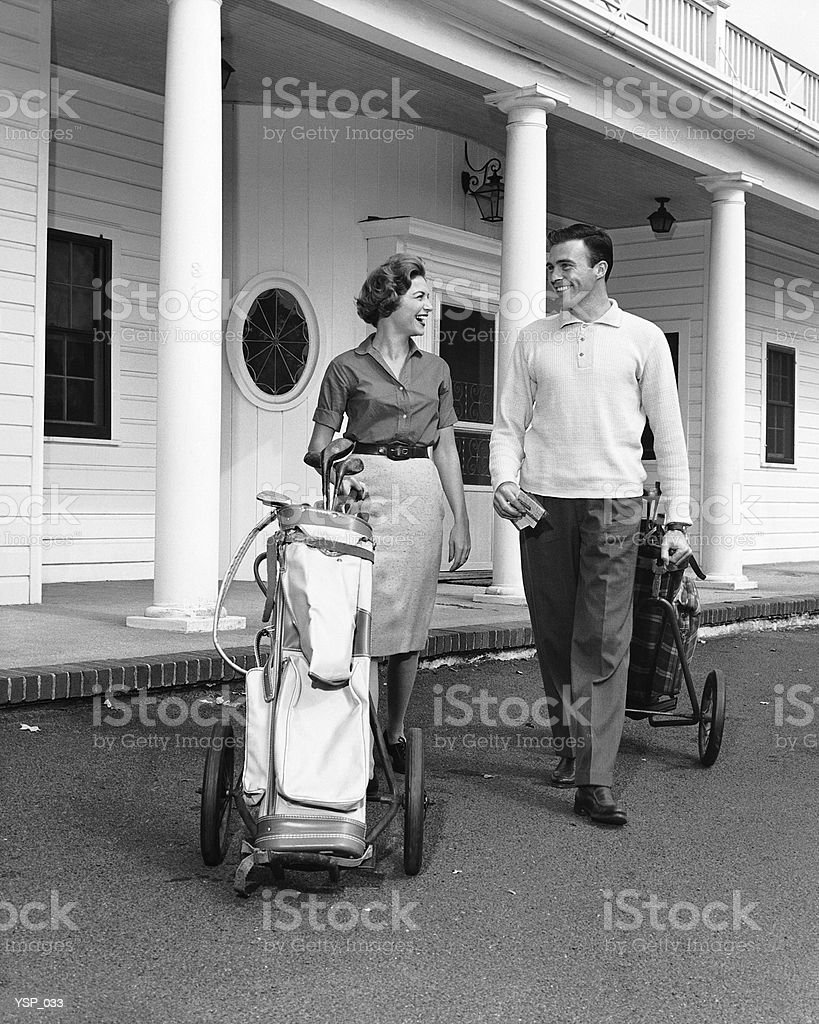 Couple walking with golf carts in front of clubhouse royalty-free stock photo