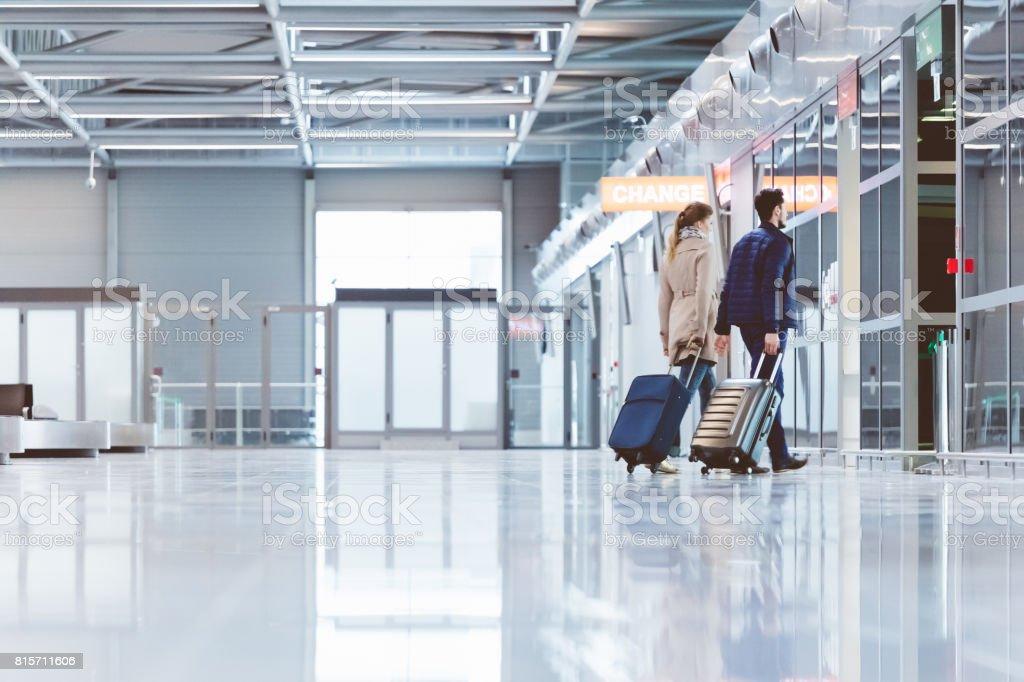 Paare, die mit Gepäck im Flughafen-terminal Lizenzfreies stock-foto