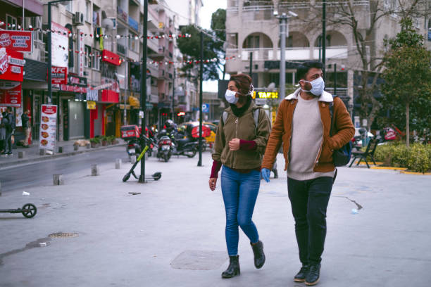 Couple walking with Protective Masks to Avoid Covid-19 Coronavirus. stock photo