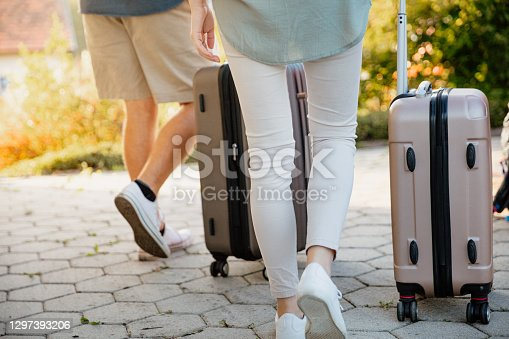 Low section of couple walking with suitcase on street