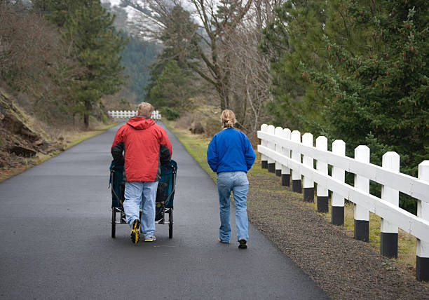 Couple walking with the double-stroller focusing on the path ahead (Hood River, Oregon trail) hood river valley stock pictures, royalty-free photos & images