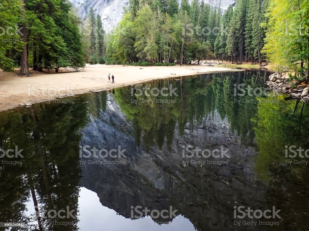 Couple Walks Along Shore of River in Yosemite Valley with Reflection of Mountains stock photo