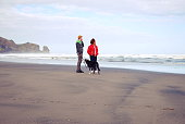A Couple Walk their Dog on a Remote West Auckland Beach in Winter, New Zealand.