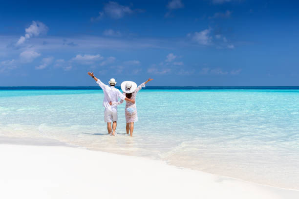 Couple walks down a tropical beach in white clothing stock photo