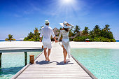 A happy traveler couple in white summer clothing walks down hand in hand a wooden pier towards a tropical paradise island in the Maldives, Indian Ocean