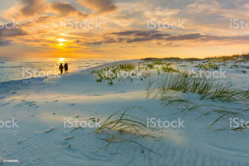 Couple walks on beach at sunset stock photo