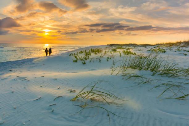 paar spaziergänge am strand bei sonnenuntergang - golfküstenstaaten stock-fotos und bilder