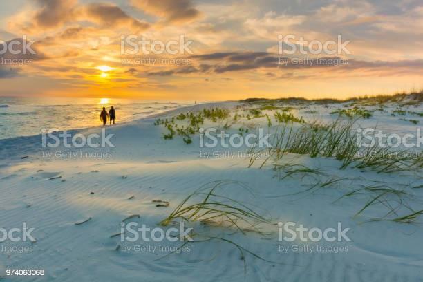 Photo of Couple walks on beach at sunset