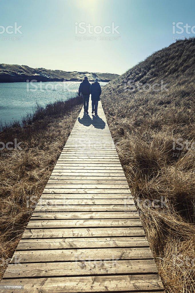 Couple walks through the dunes stock photo