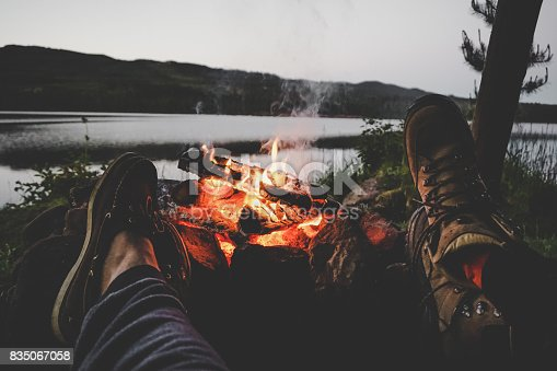 Young couple holding their feet on a fire with a lake in the background.