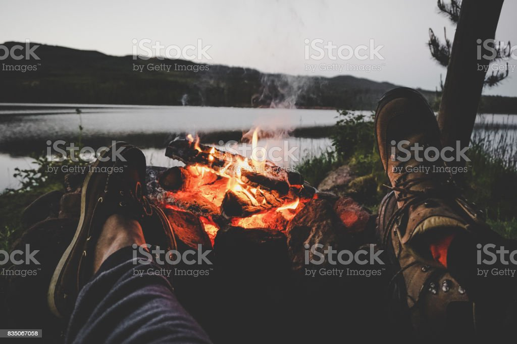 Couple warming their feet on camp fire stock photo