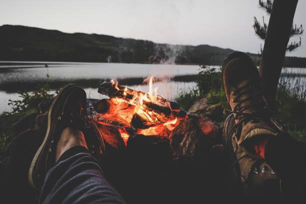 couple warming their feet on camp fire - falò foto e immagini stock
