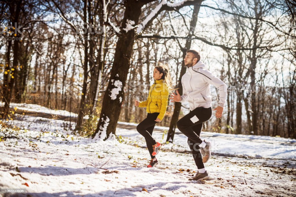 Couple warming up before running in nature. Winter and cold weather.