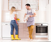 Happy young couple washing and wiping dishes together in kitchen