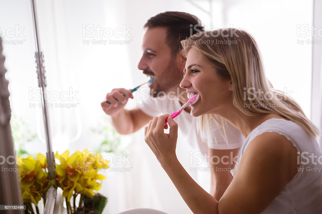 Couple washing teeth in morning stock photo