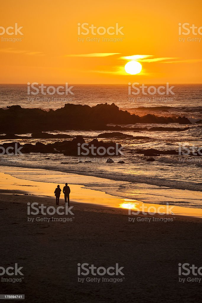 Couple watch the sunset at Carmel Beach in Carmel-by-the-Sea royalty-free stock photo