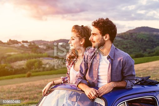 A loving couple, on a summer afternoon, watching sunset from the roof of an old car, around the classical landscape of Tuscany, vineyards and farmland. The two lovers come out from the car roof