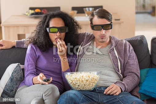 Young couple eating popcorn while watching 3D television at home.