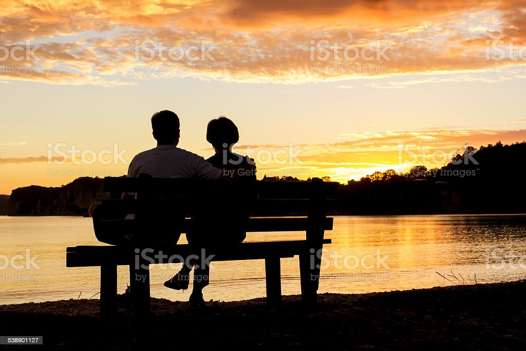 Couple watching a beautiful sunset together - Royalty-free 2015 Stock Photo