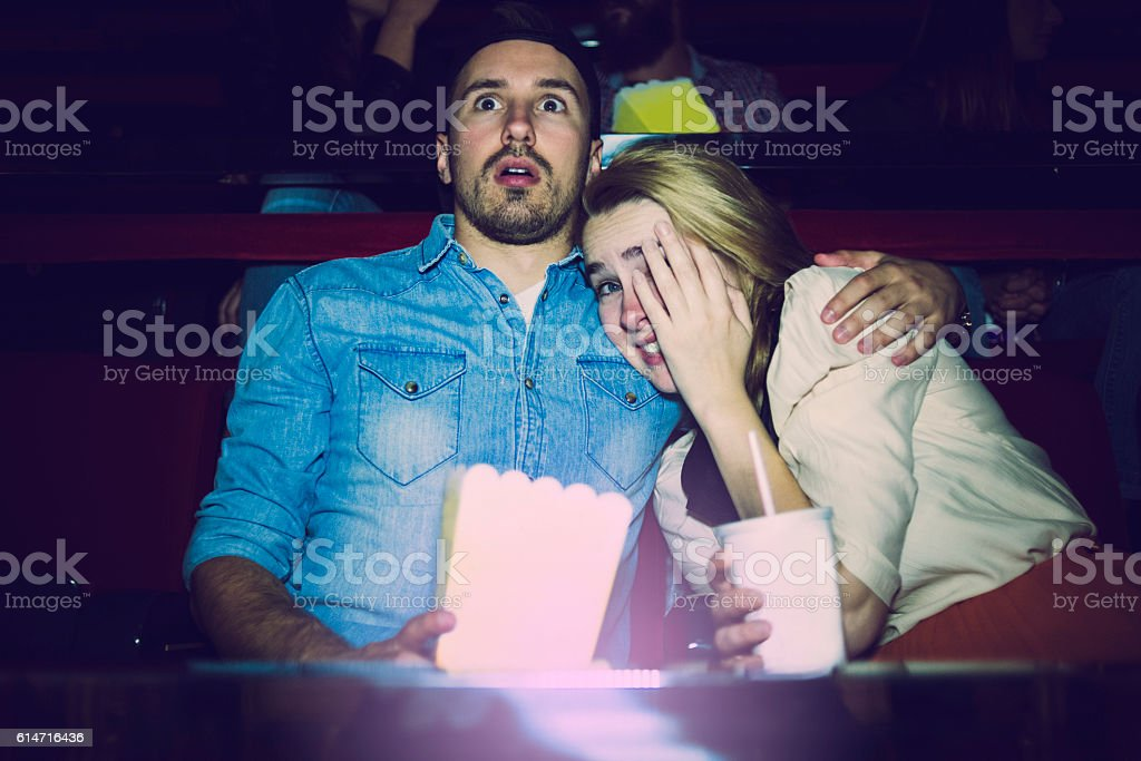 couple watching a horror movie in the cinema stock photo
