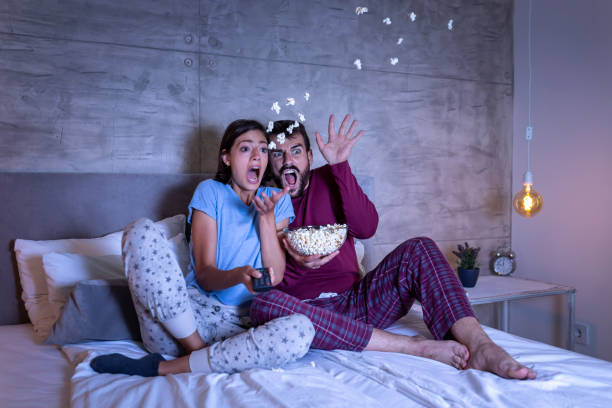 Couple watching a horror movie stock photo