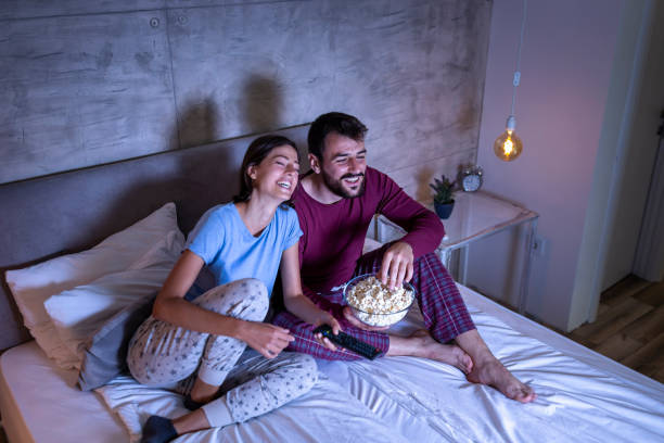Couple watching a movie in bed stock photo