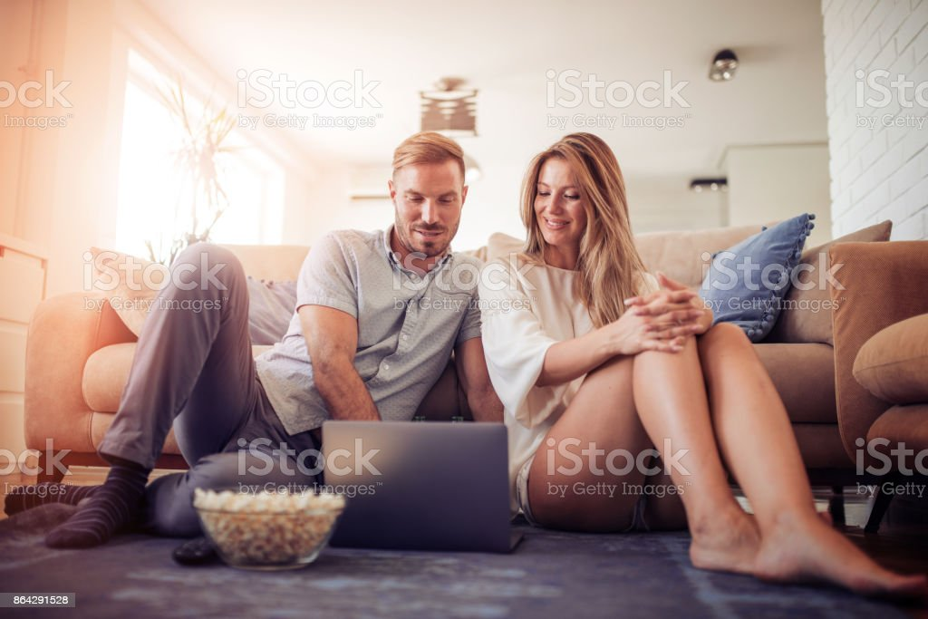 Couple watching a movie on laptop in their living room royalty-free stock photo