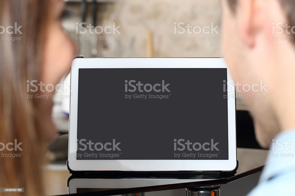 Couple watching and showing a blank tablet screen stock photo