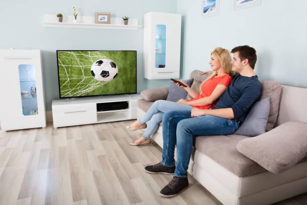 paar fußballspiel im fernsehen anschauen - fußball themenzimmer stock-fotos und bilder