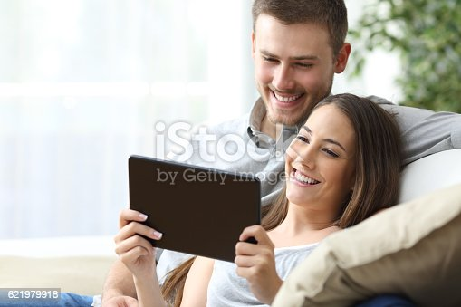 Casual couple watching media content on line in a tablet sitting on a sofa in the living room at home