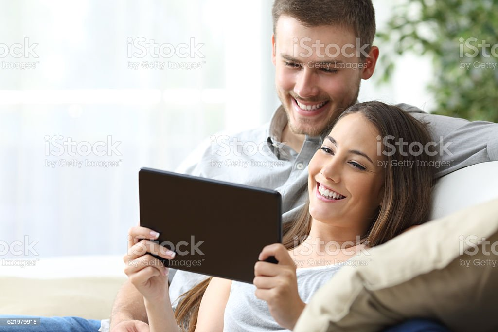 Couple watching media in a tablet stock photo