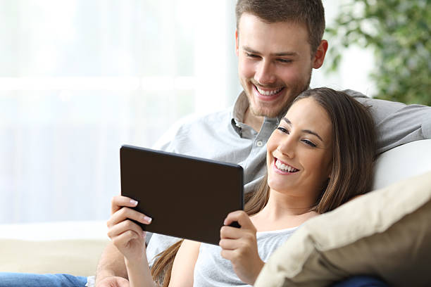 couple watching media in a tablet - filme sehen stock-fotos und bilder
