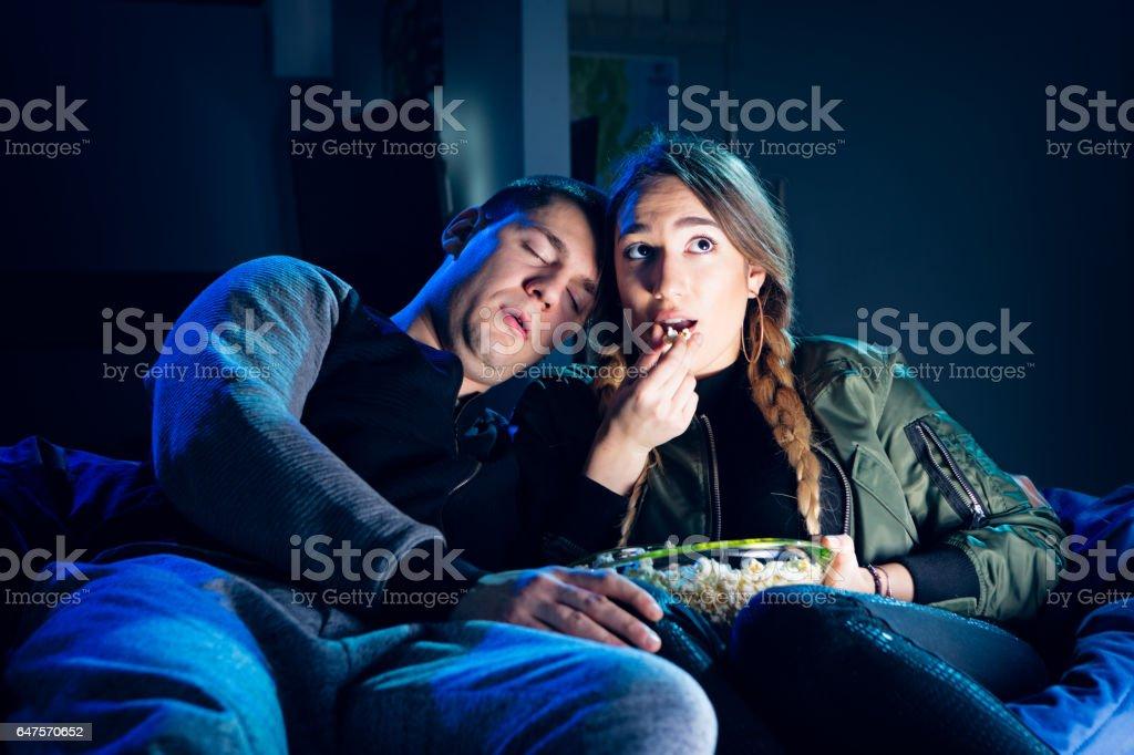 Couple watching movie, eating popcorns stock photo
