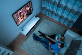 High Angle View Of Couple Watching Movie In Living Room